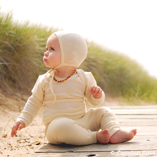 Organic baby wearing soft, warm pants, shirt, and cap in organic wool, silk, and cotten.